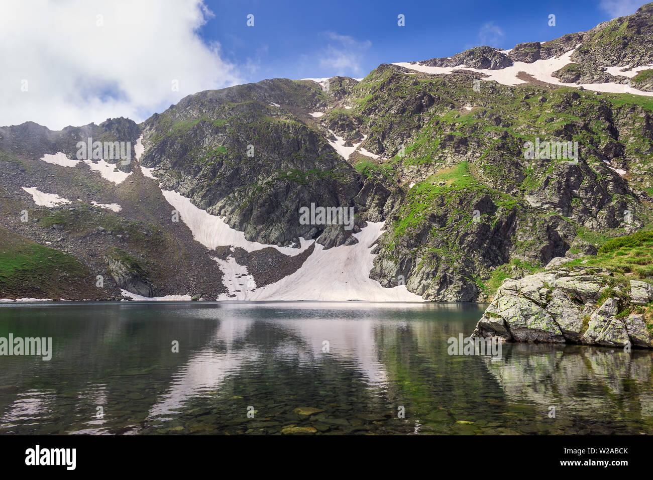 La pasto verde sobre un altiplano rocoso y picos del macizo de Rila y el reflejo en el agua limpia del Ojo del lago glacial, uno de los siete lagos de Rila Foto de stock