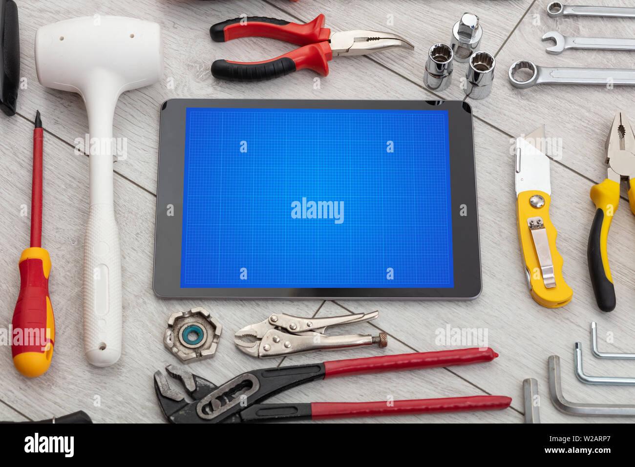 Las herramientas de la casa y tablet con pantalla de cuadrícula concepto Foto de stock