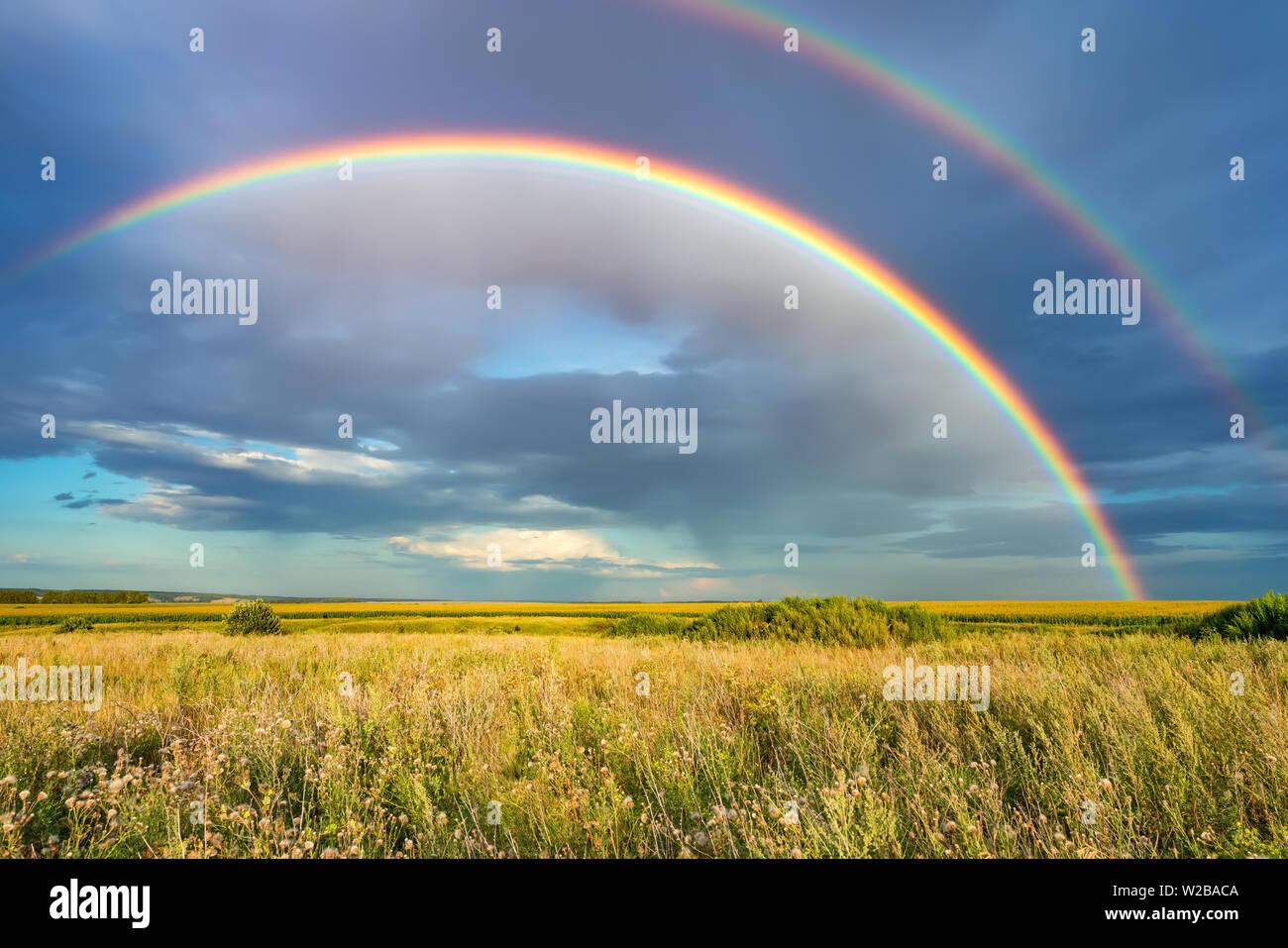Arco iris sobre cielo tormentoso en medio del campo, en día de verano Foto de stock