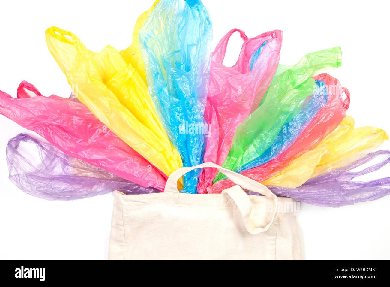 Muchas bolsas de plástico de un solo uso en un eco natural bolsa de compras reutilizable sobre fondo blanco. Cero residuos, respetuoso con el medio ambiente, la sostenibilidad, el estilo de vida no plas Foto de stock