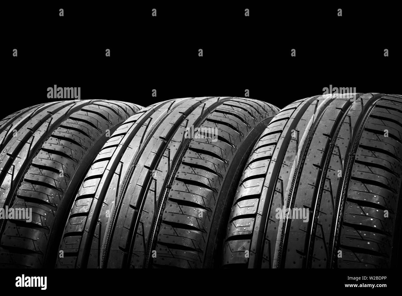 Foto de estudio de un juego de neumáticos de verano aislado sobre fondo negro. Antecedentes La pila de neumáticos. Neumático de coche protector de cerca. Neumático de caucho negro. Marca ne Foto de stock