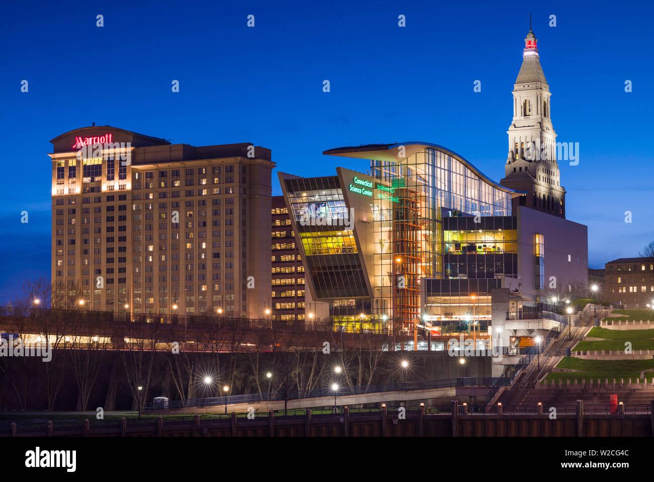 Estados Unidos, Connecticut, Hartford, Connecticut con vistas al horizonte de la ciudad y los viajeros del Centro de Ciencias de la construcción, desde el río Connecticut, al anochecer Foto de stock