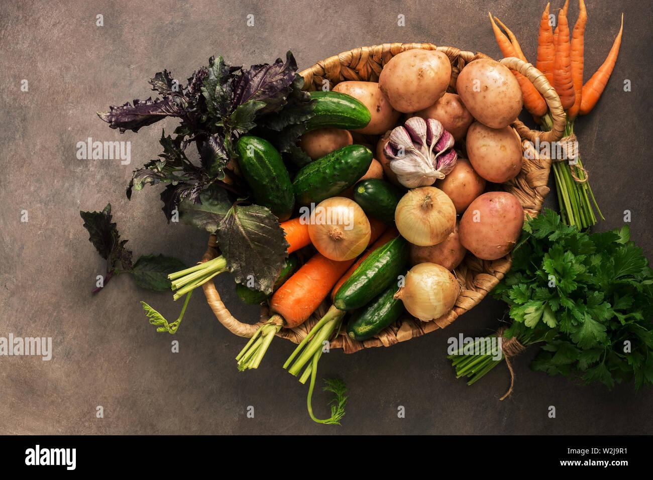 Verdura cruda fresca de la nueva cosecha, patatas, cebollas, zanahorias, pepinos, ajo, perejil y albahaca en una cesta en un oscuro fondo rústico. Top vie Foto de stock