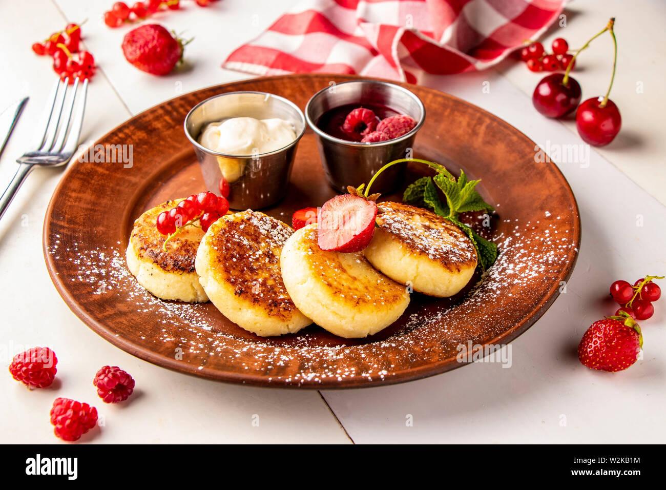 Requesón tortitas, plato tradicional ucraniana syrniki casero con salsa de frambuesa y crema agria en una placa marrón sobre un fondo blanco. Foto de stock