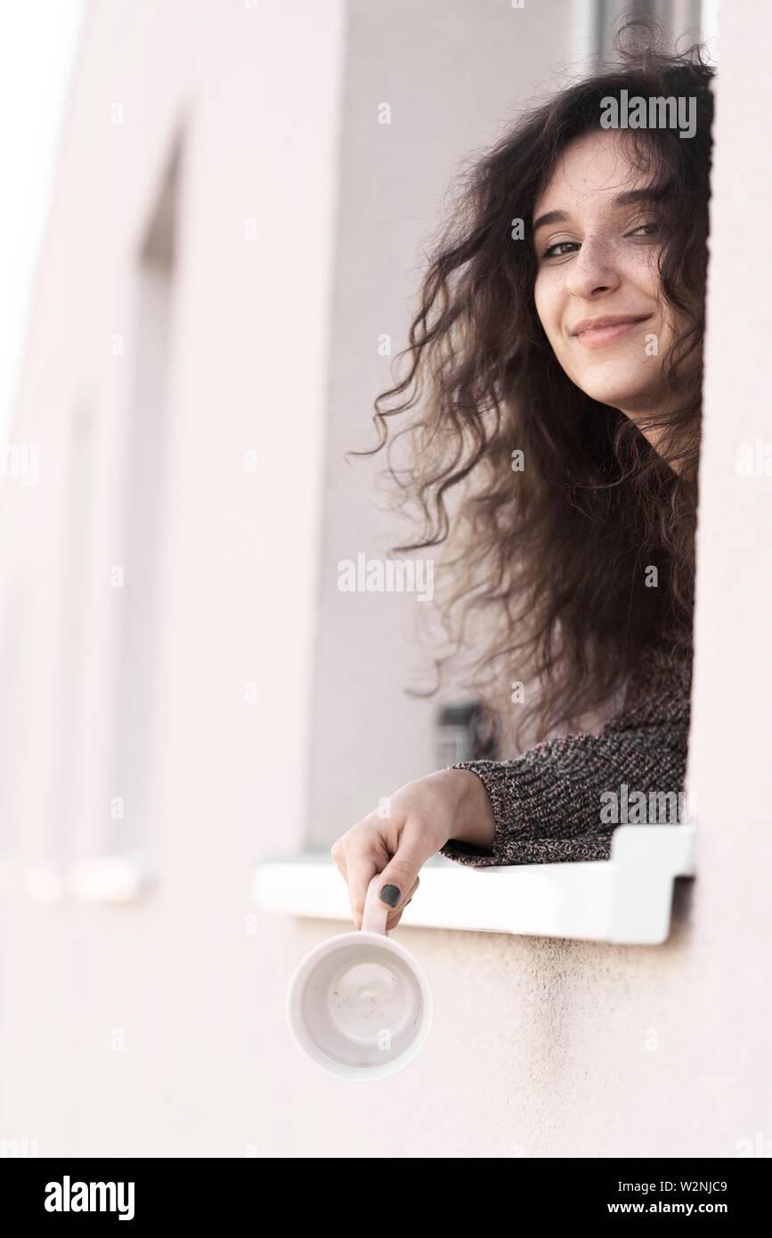 Contenido joven mujer mirando por la ventana de su casa Imagen De Stock