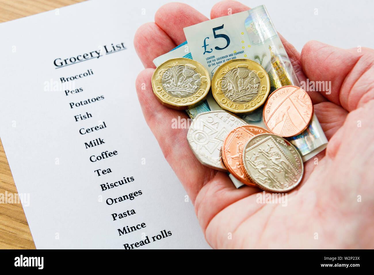 Un pobre pensionista senior de la mano que sostiene una pequeña cantidad de dinero nuevo GBP con una lista de compras para el supermercado la pobreza concepto de austeridad Inglaterra Gran Bretaña Imagen De Stock