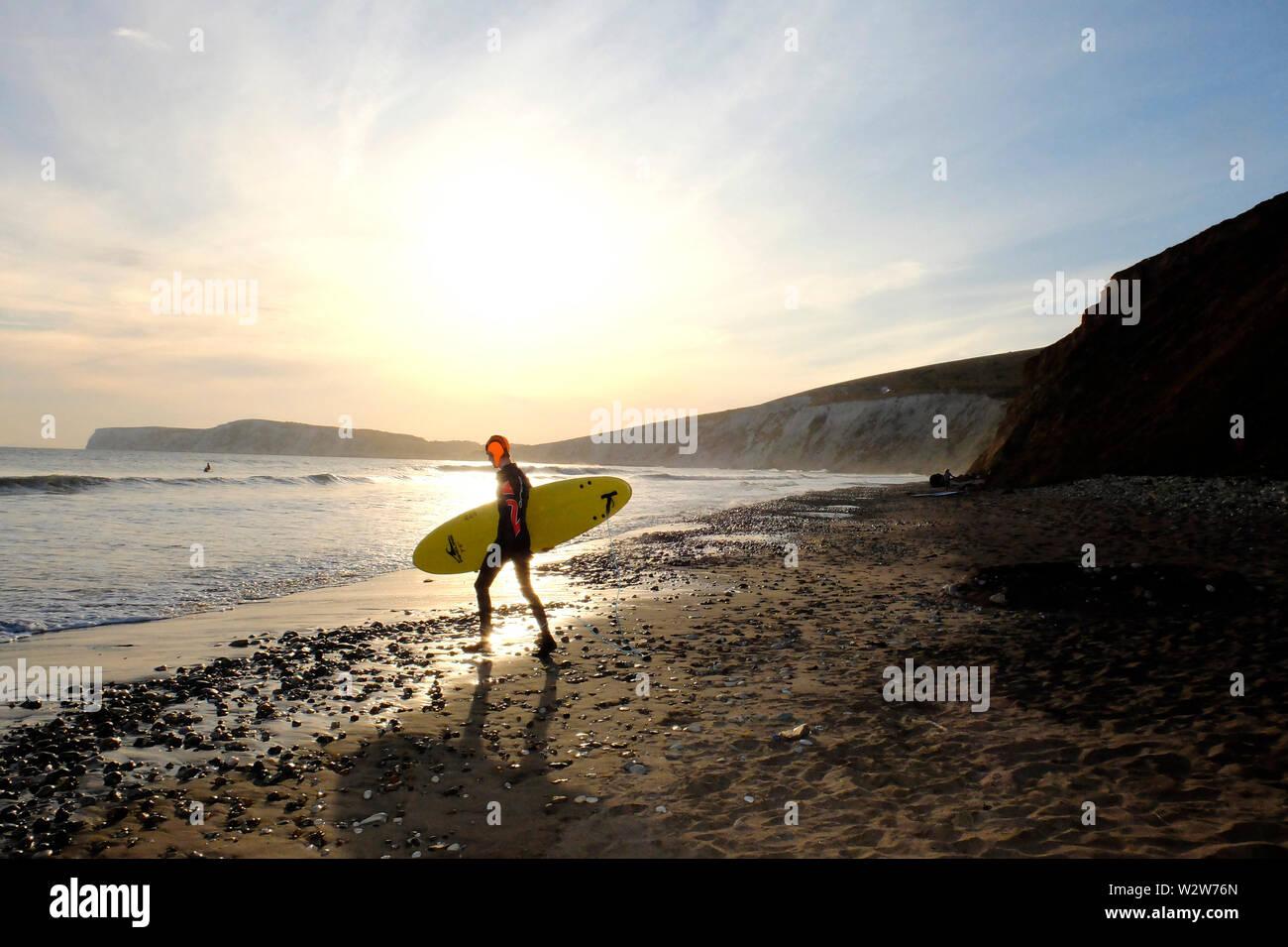 Un hombre joven llevando su tabla de surf bajo el brazo, los jefes en el mar a pie con la puesta de sol y Tennyson abajo rocas calcáreas en el fondo Foto de stock