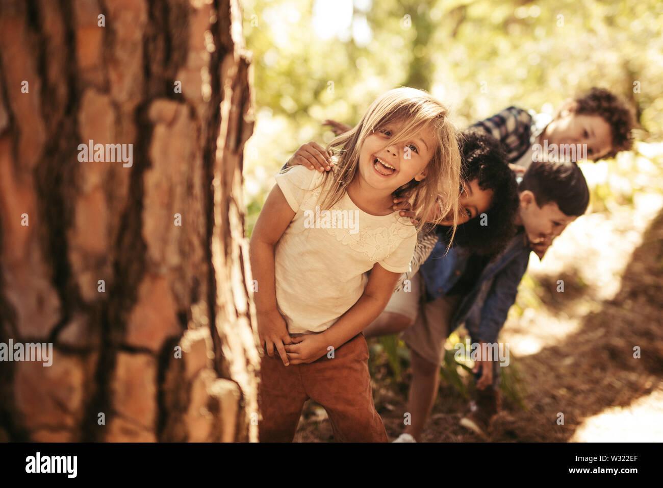 Grupo de chicos de pie en fila detrás de un árbol y mirar afuera. Niños jugando al escondite en un parque. Foto de stock
