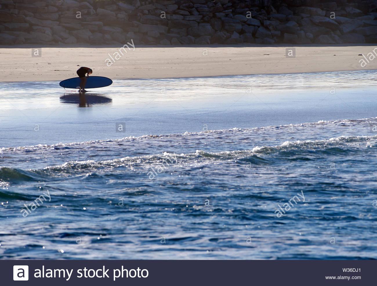 Una silueta surfer inclinó su junta sobre la playa, se prepara para entrar en el agua; en el Invitacional longboarding Yamba Aleta simple competencia. Foto de stock