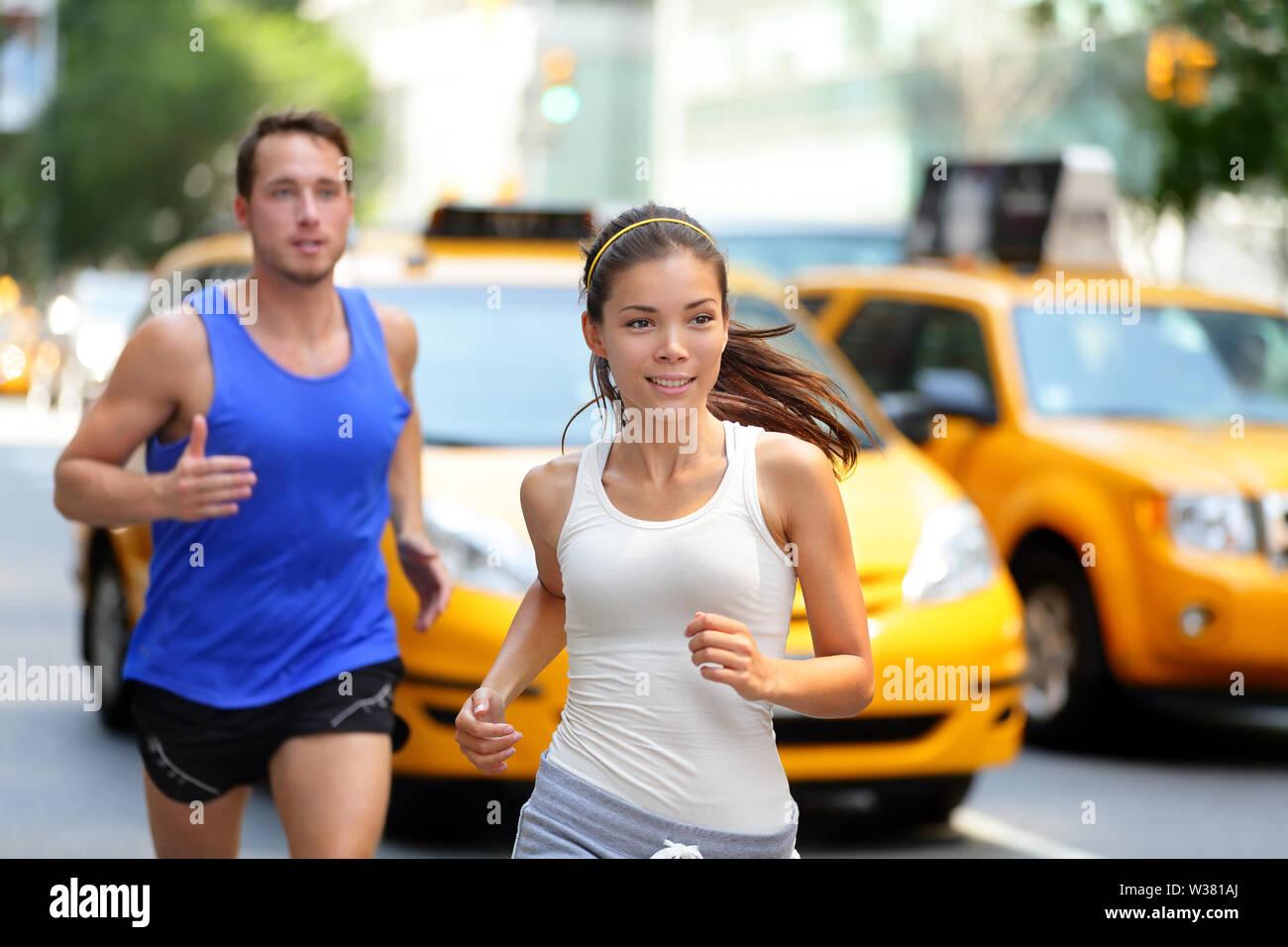 Pareja activa girando en la famosa calle de tiendas de la quinta avenida en Manhattan, Ciudad de Nueva York NUEVA YORK, ESTADOS UNIDOS. Ejercicio estilo de vida retrato de joven mujer asiática runner y caucásicas emparejador masculinos. Foto de stock