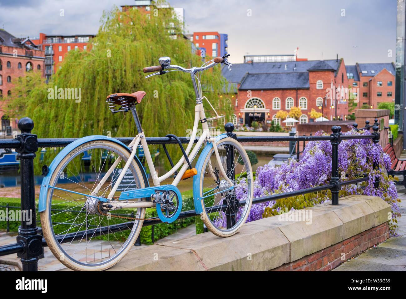 Manchester, Reino Unido - 25 de abril de 2019: Escena atmosférica de una bicicleta estacionada en el sistema de canal Victoriano restaurado en área de Castlefield Manc Foto de stock
