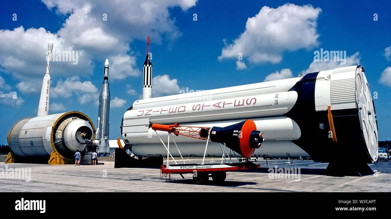 Una maqueta de una nave espacial Proyecto Mercurio, como el que se llevó el primer astronauta norteamericano en el espacio exterior en 1961, fue en la pantalla al aire libre, en el Centro Espacial Kennedy, cerca de Cabo Cañaveral en Florida, Estados Unidos, cuando se tomó esta fotografía 15 años más tarde. La cápsula en forma de cono es eclipsado por los cohetes de refuerzo en el fondo que se utiliza para lanzar diversas misiones espaciales. En la actualidad la cápsula Mercury original que tuvo Alan B. Shepard Jr. en su histórico vuelo se encuentra en el Smithsonian National Air and Space Museum en Washington, D.C. fotografía histórica. Foto de stock