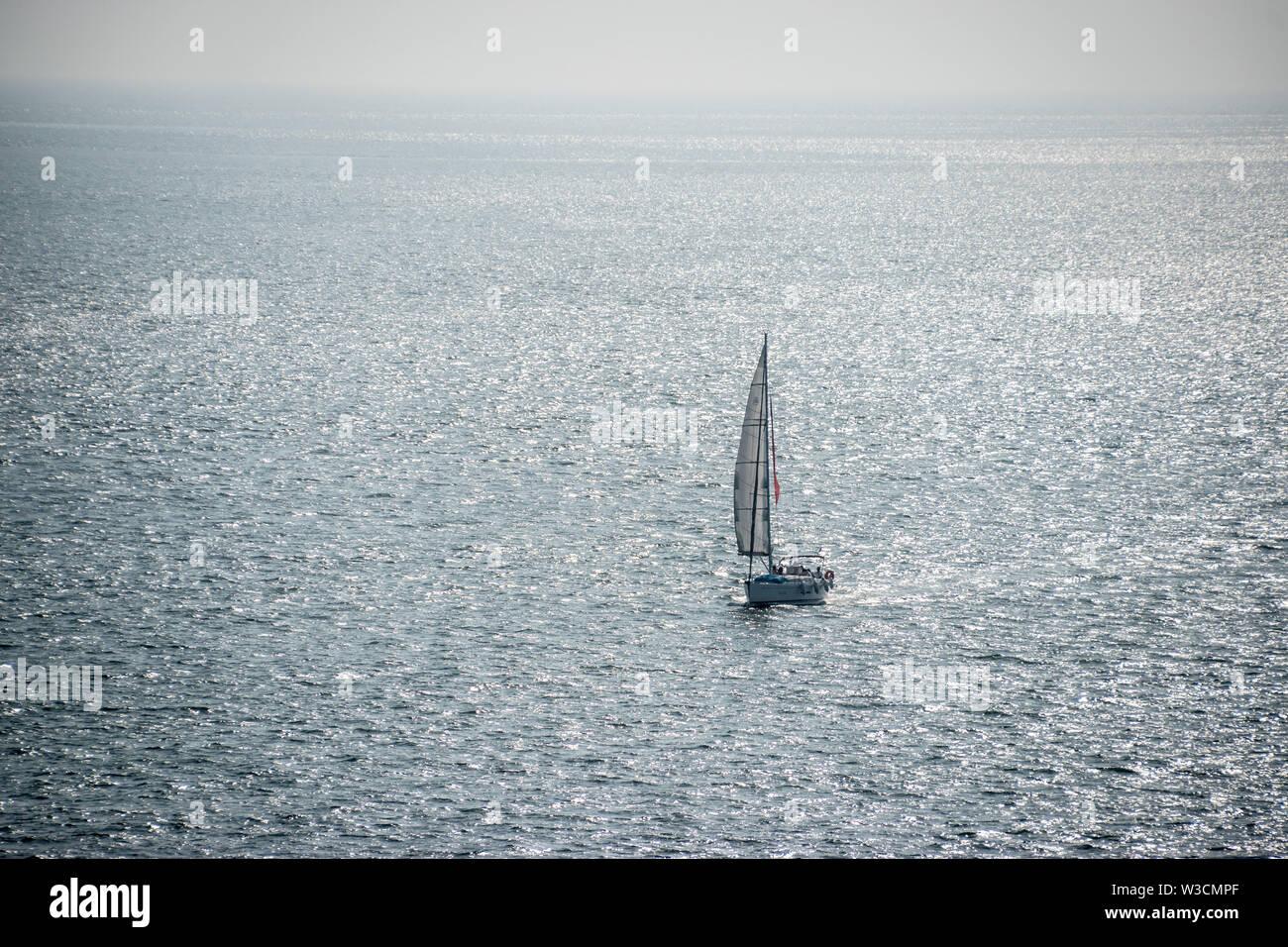 Un solitario único velero en el Océano Atlántico frente a la costa de Lisboa, Portugal. Foto de stock