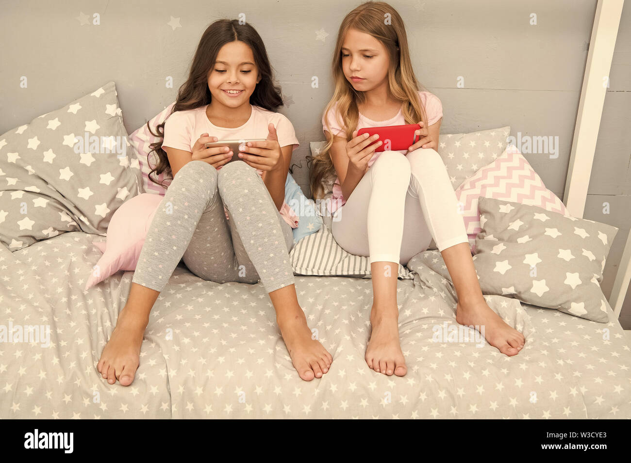Smartphone para entretenimiento. Kids Play móvil smartphone aplicación de juego. Concepto de aplicación de Smartphone. Ocio Girlish Pajama Party. Las niñas poco smartphone bloggers. Explore la red social. Foto de stock