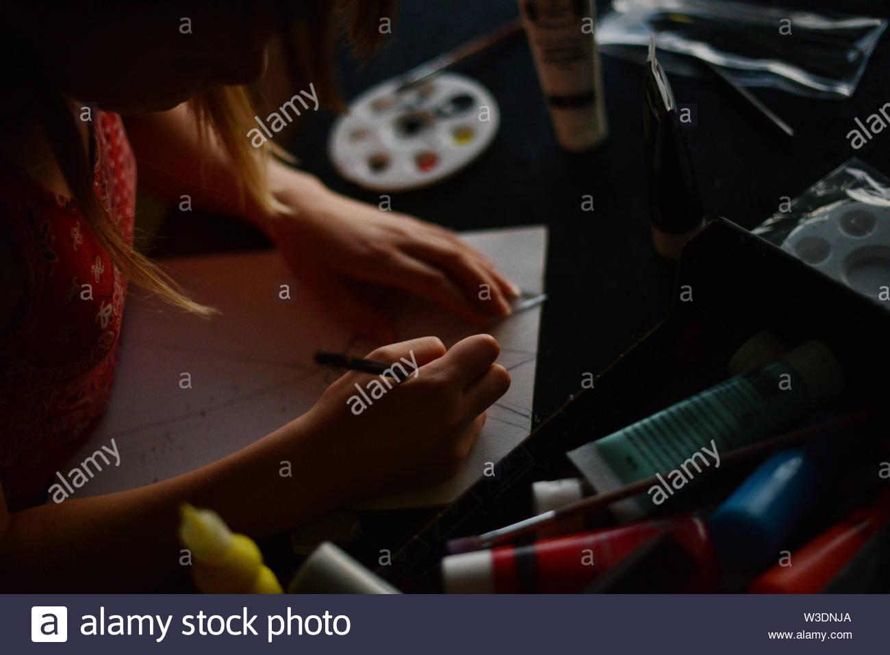 Dibujo de una niña con un lápiz sobre una hoja de papel blanco. La pintura suministros en tubos alrededor de ella en un escritorio negro Foto de stock