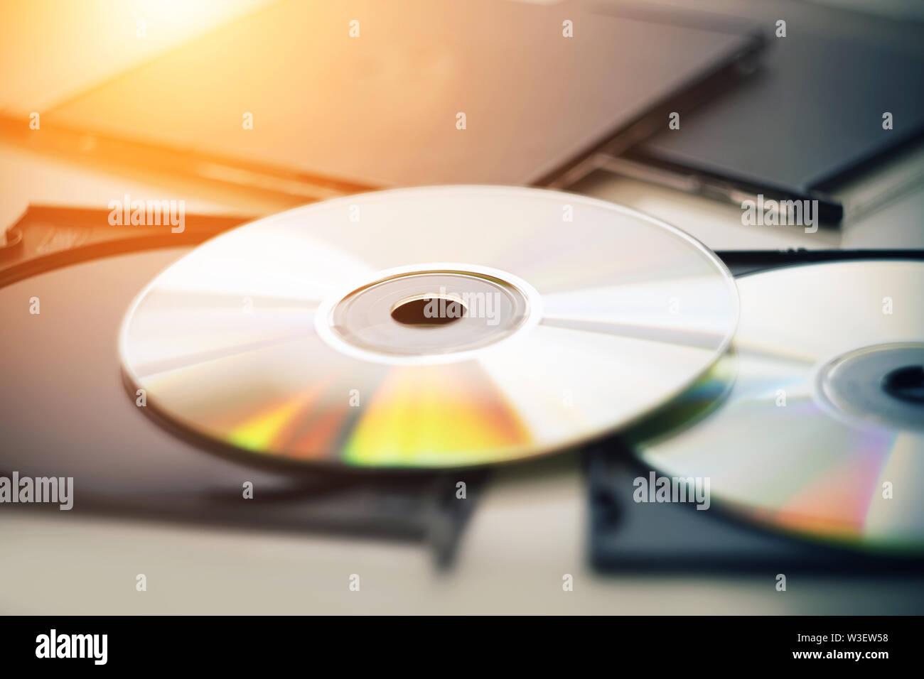 Dos nuevos discos compactos se encuentran junto a las cajas negras de los discos, y está iluminado por la luz del sol, desde el cual los discos brillan en diferentes col Foto de stock