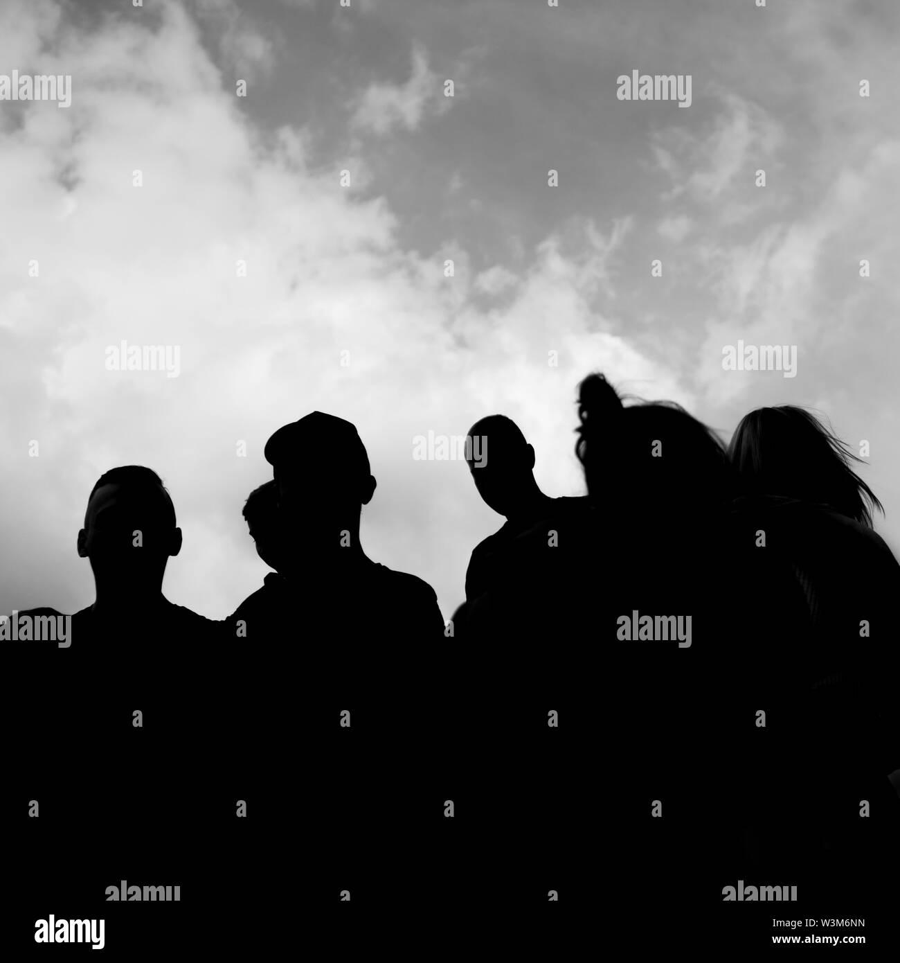 Una simple silueta oscura de un grupo de personas con el cielo y las nubes en el fondo Imagen De Stock