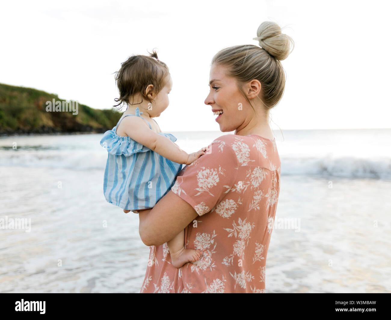 Mujer sosteniendo hijita en la playa Foto de stock