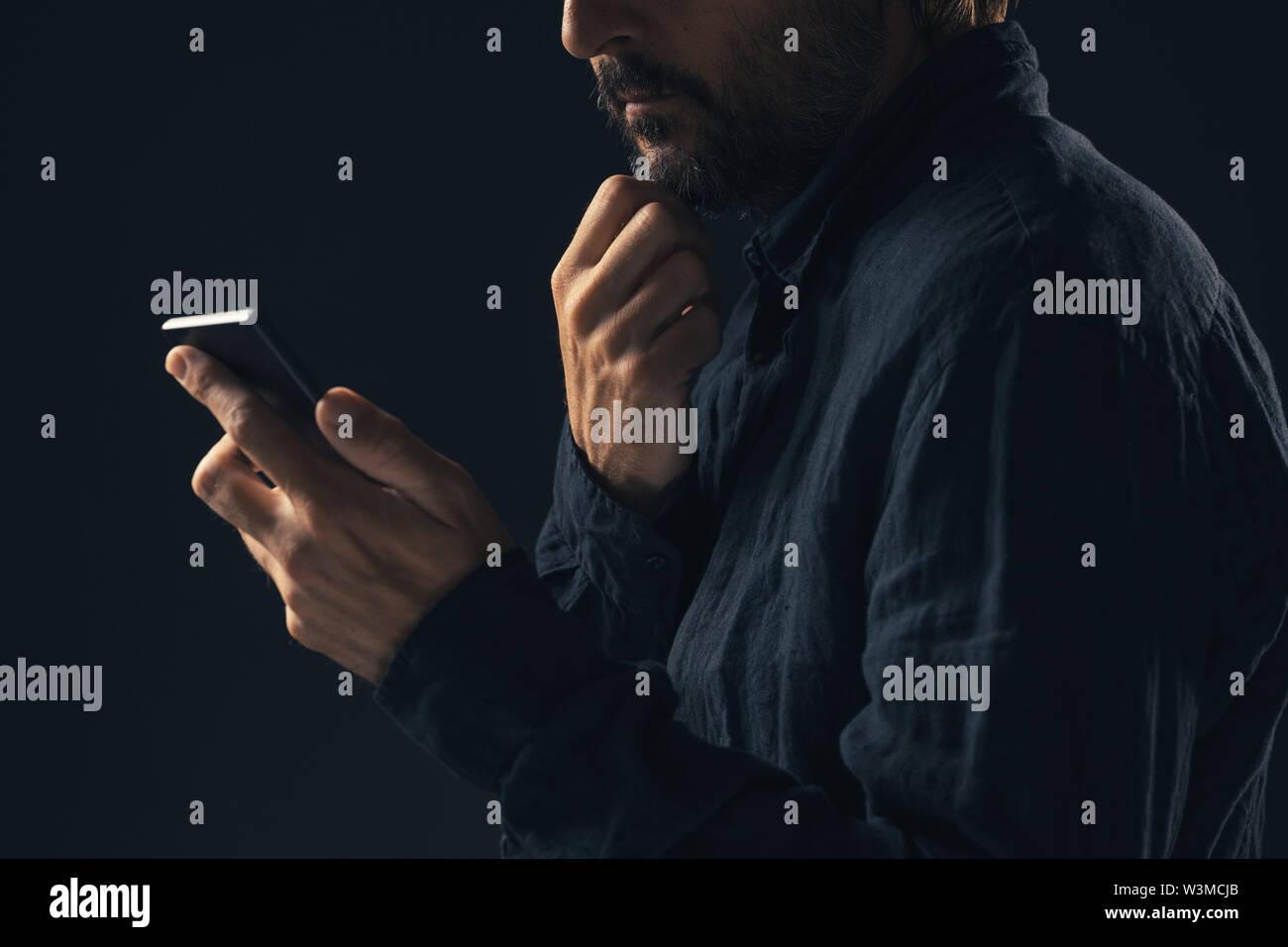 Reflexivo preocupado el hombre está leyendo el texto del mensaje en el smartphone Imagen De Stock