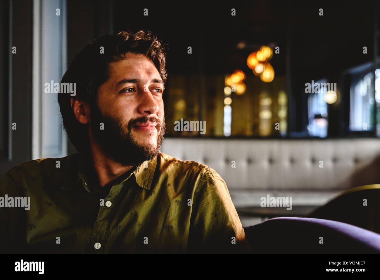 Joven con barba latino mirando al infinito pensando en los futuros negocios. Imagen De Stock