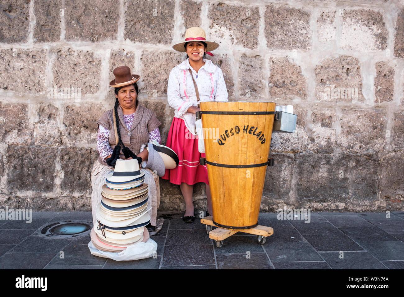 Los vendedores ambulantes. Las mujeres venden el queso helado (queso helado) y sombreros vestida con ropa tradicional peruano, Arequipa, Perú. Imagen De Stock