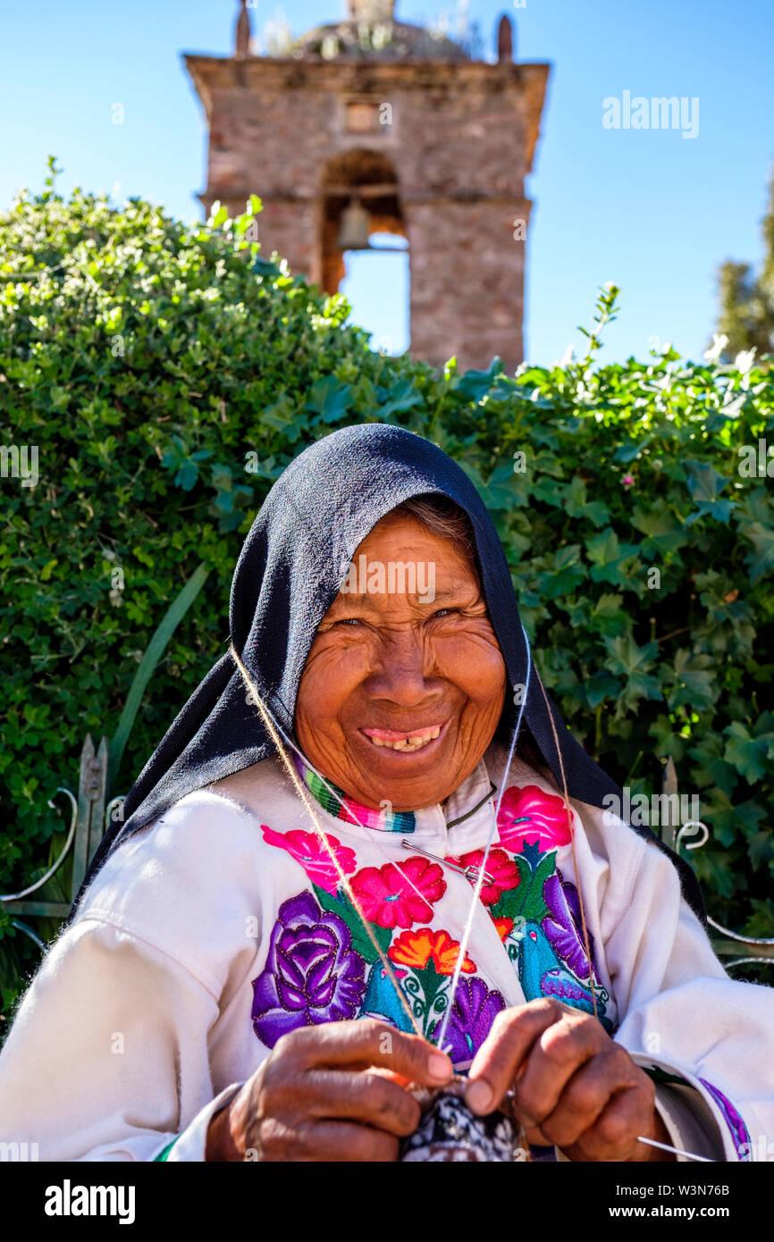 Retrato de ancianos mujer Quechua vistiendo ropa tradicional peruana, tejer, sonriente, Isla de Amantani, Lago Titicaca, Perú Imagen De Stock