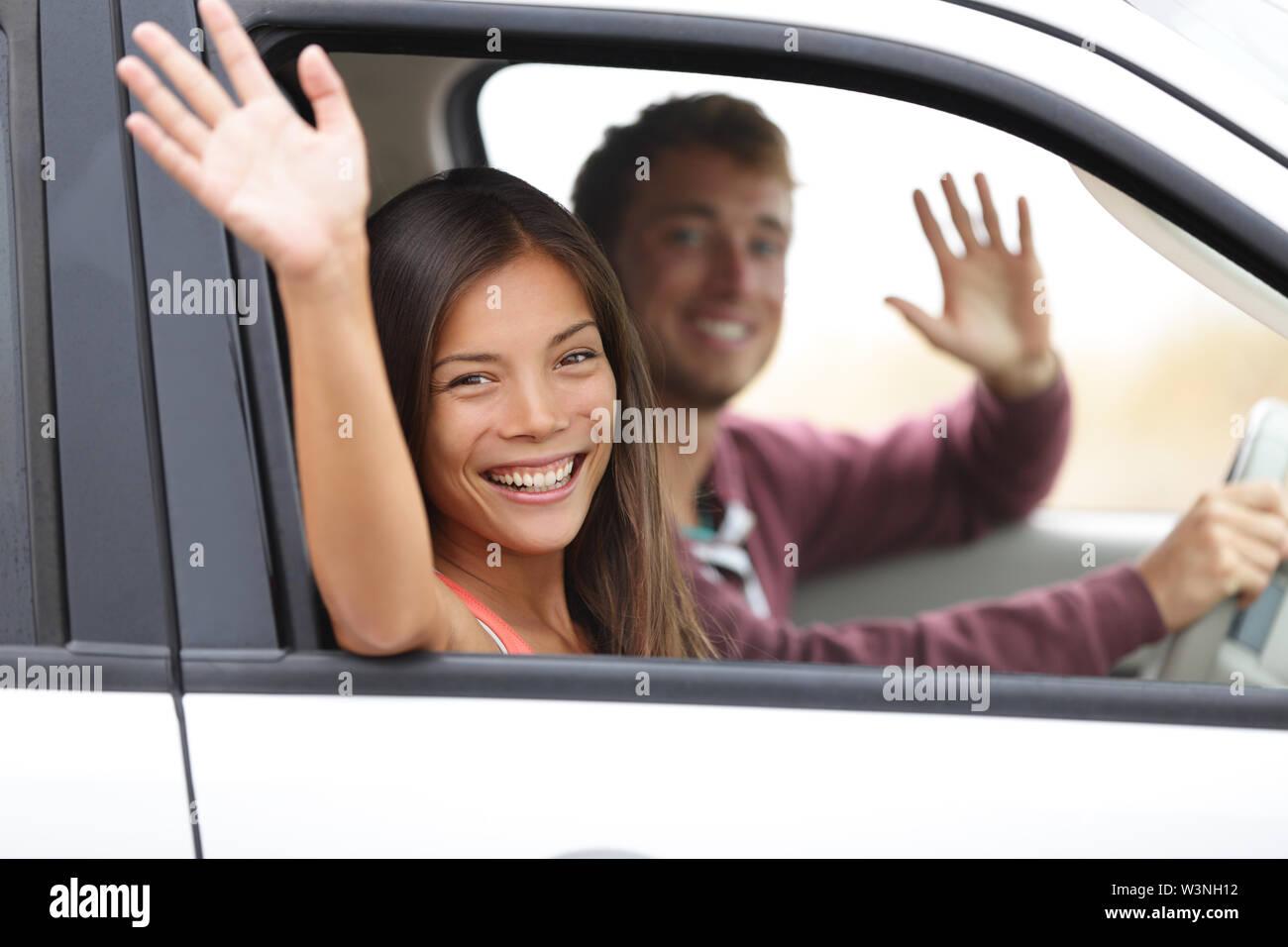Los conductores conducir en coche ondeando feliz en la cámara. Pareja joven en viaje por carretera en coche nuevo. Feliz pareja interracial. Imagen De Stock