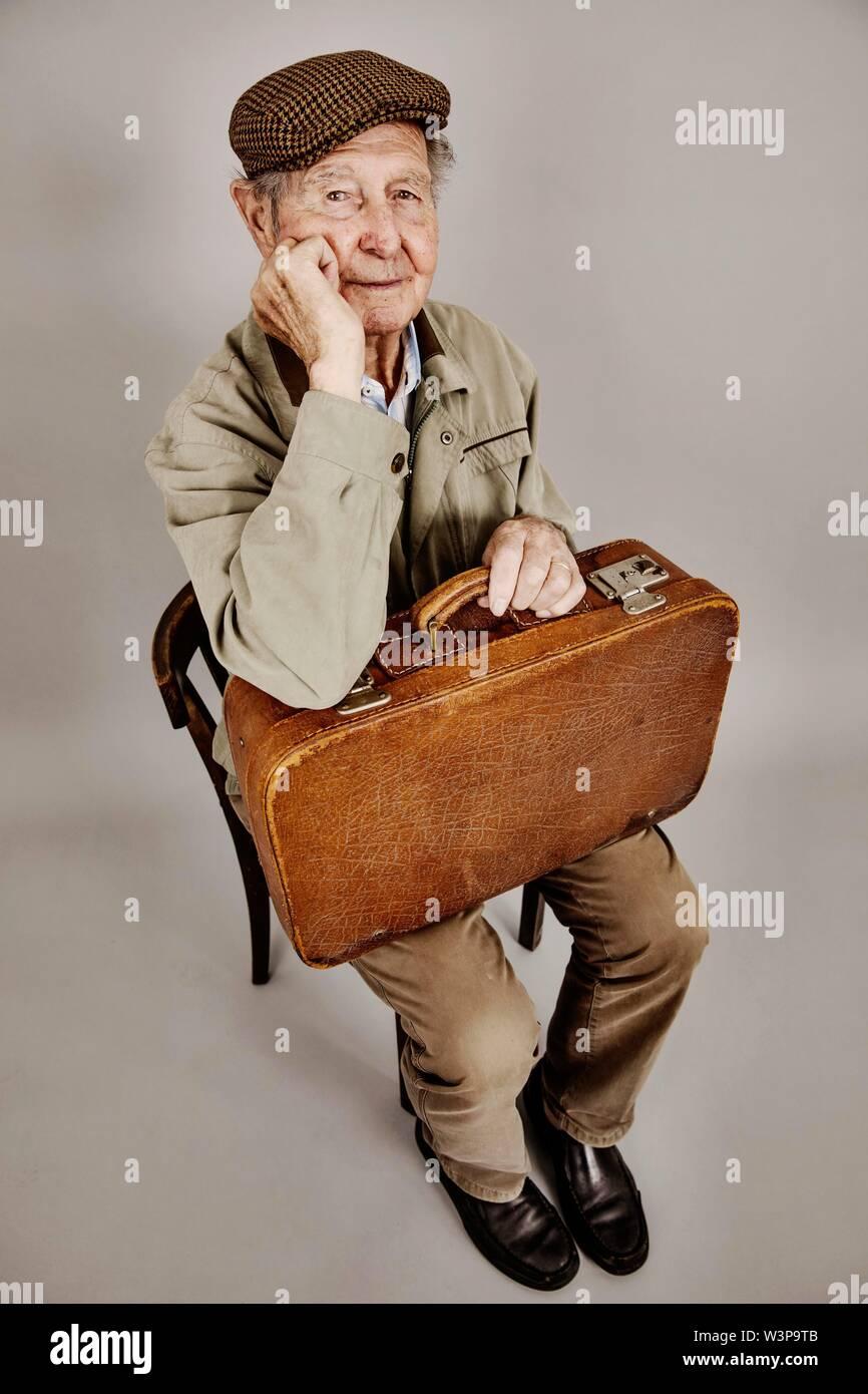Altos se sienta con la vieja maleta sobre una silla, dejando la imagen simbólica, nostalgia, Foto de estudio, Alemania Imagen De Stock