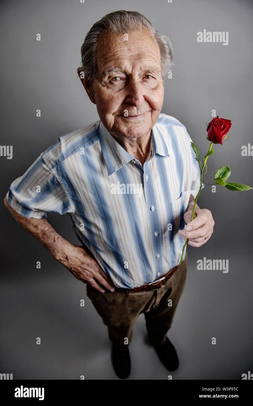 Altos tiene una rosa roja en la mano, imagen símbolo de amor, romance, Foto de estudio, Alemania Imagen De Stock