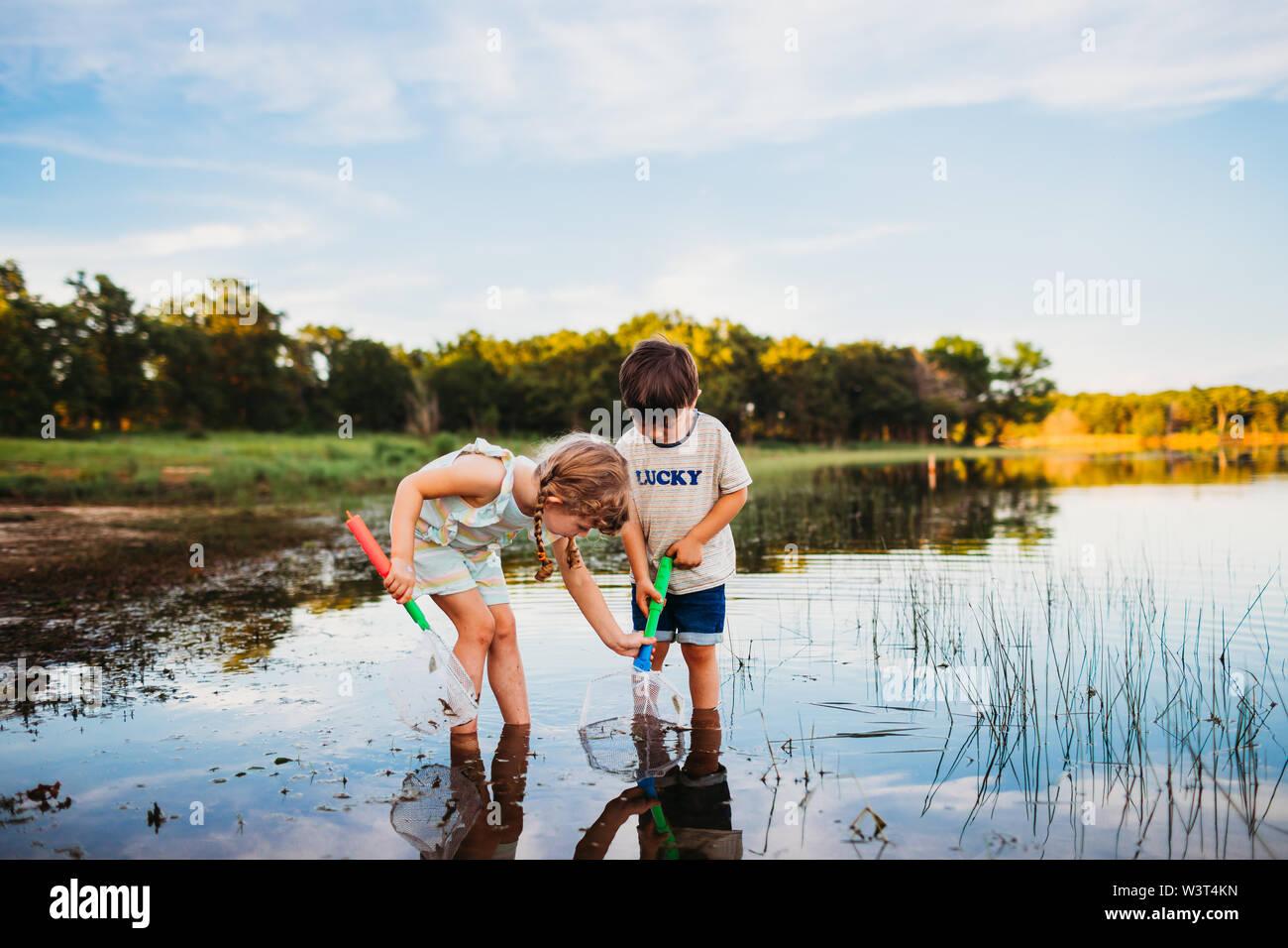 Niña ayudando a boy atrapar un pez en su red en el lago Foto de stock