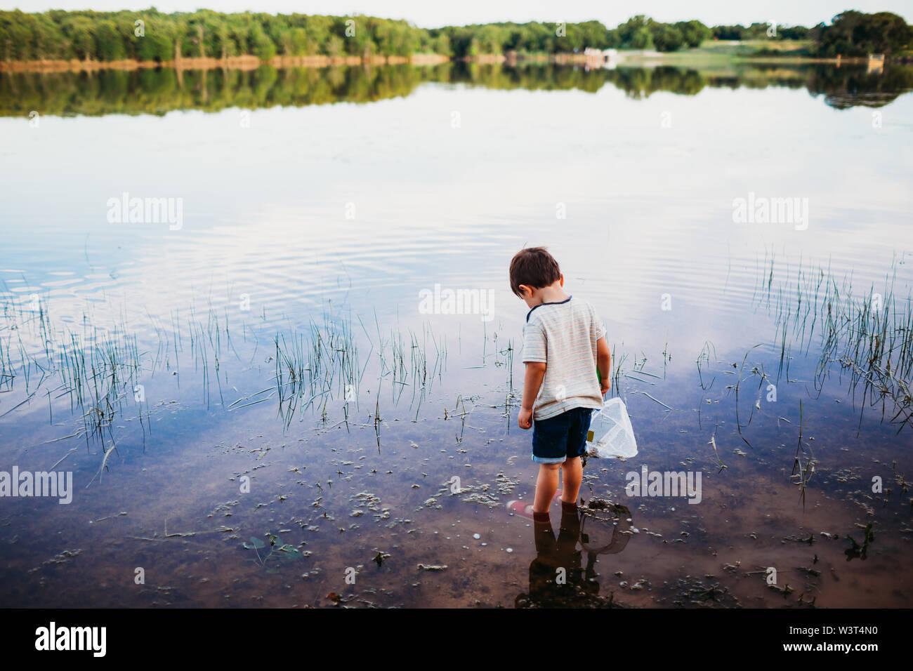 Joven de pie en el lago solo buscando pescado Foto de stock