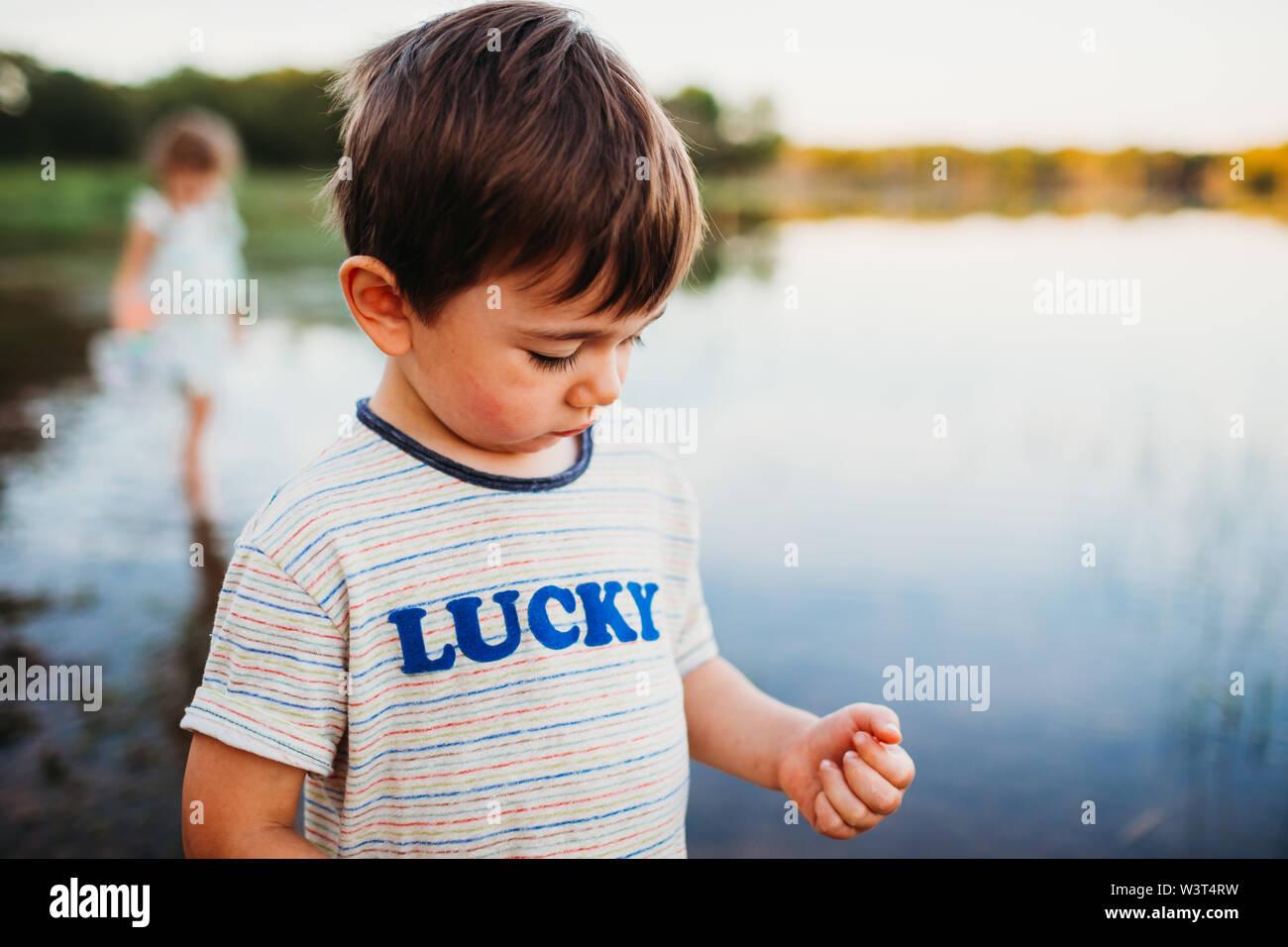 Primer plano de un joven de pie en el agua en el lago en verano Foto de stock