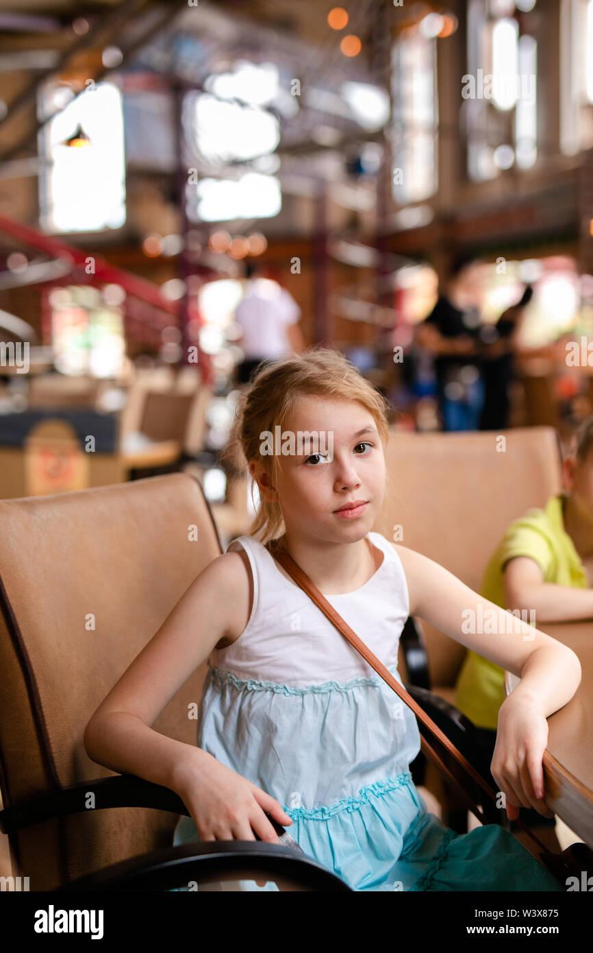 Chica rubia en vestido blanco y azul de almorzar en el restaurante. Rusia, Sochi, Sochi-park, junio de 2018. Imagen De Stock