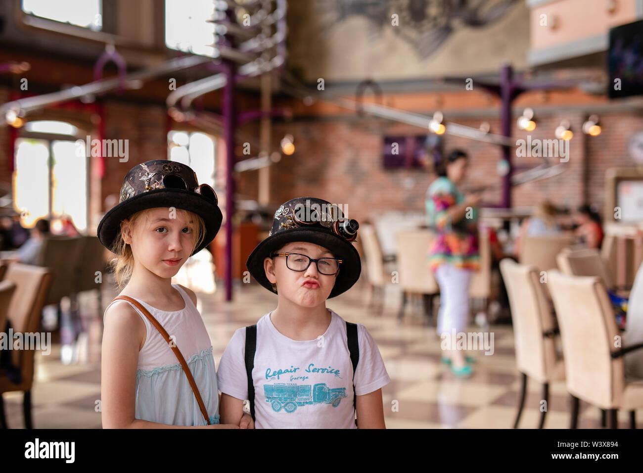 Chico y chica rubia en los sombreros divertidos. Rusia, Sochi, Sochi-park, junio de 2018. Imagen De Stock