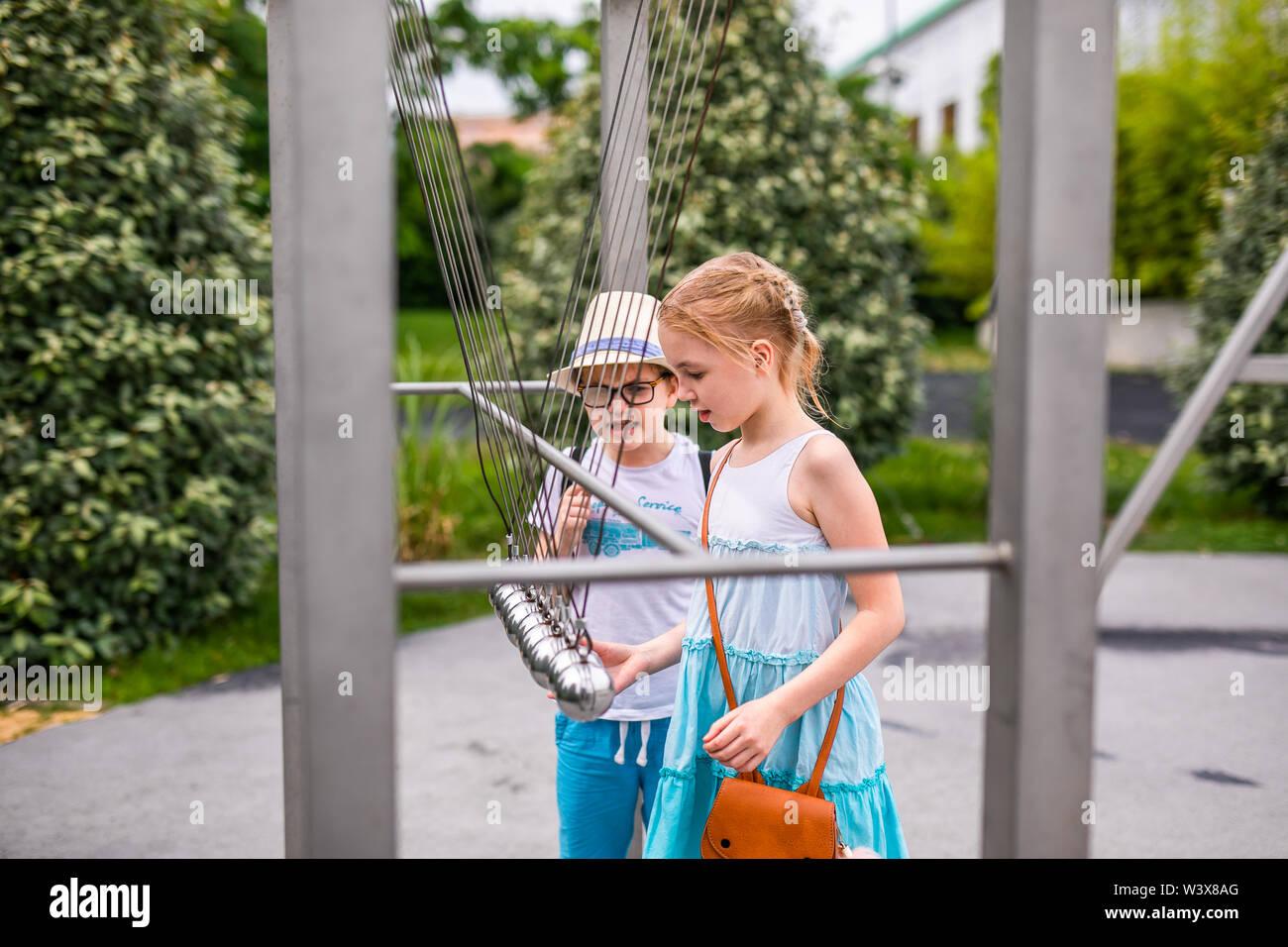 Chica rubia en vestido blanco y azul jugando en el patio de recreo en el verano parque de entretenimientos. Rusia, Sochi, Sochi-park, junio de 2018. Imagen De Stock