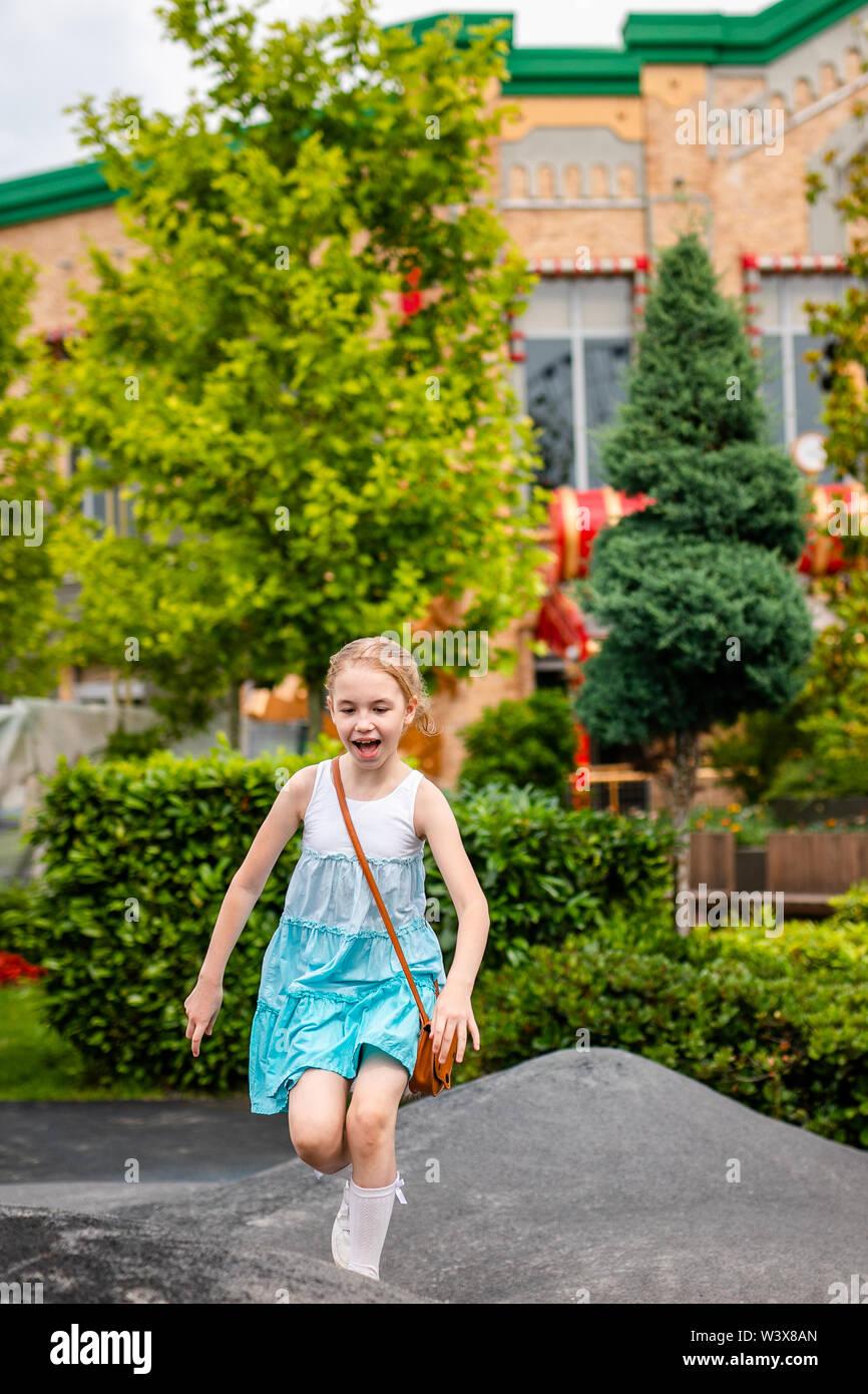 Chica rubia jugando y corriendo en el patio de recreo en el parque. Rusia, Sochi, Sochi-park, junio de 2018 Imagen De Stock