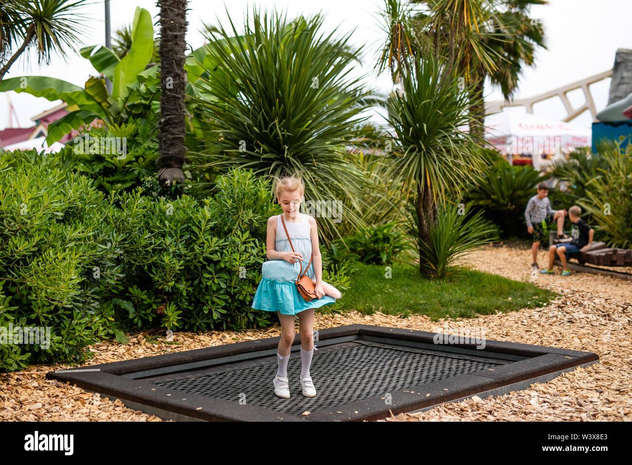 Chica rubia en vestido blanco y azul jugando en el patio de recreo en el verano parque de entretenimientos. Rusia, Sochi, Sochi-park, junio de 2018 Imagen De Stock