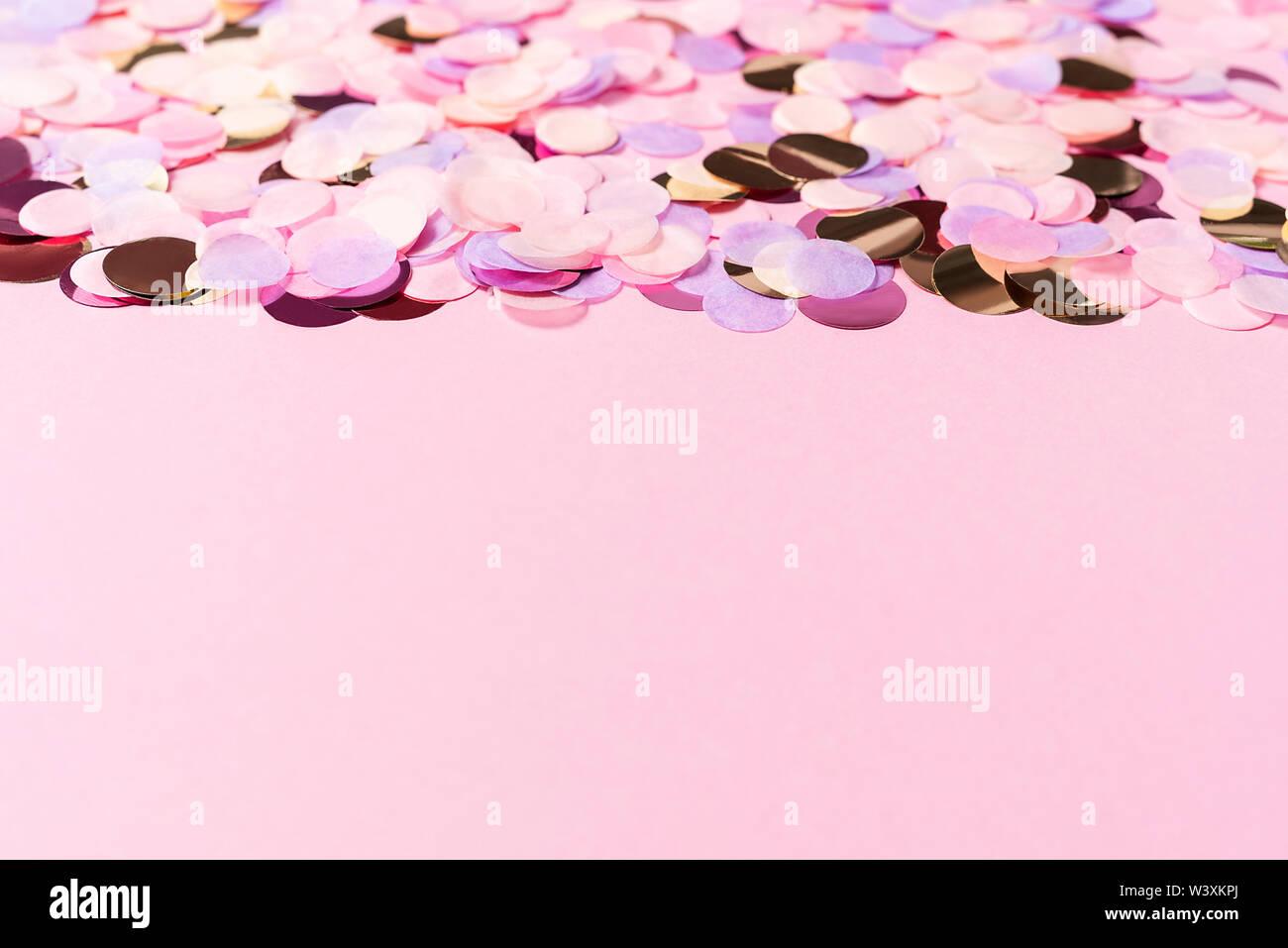 Fondo de color rosa pastel con coloridas mesas confetti de papel. Copie el espacio. Concepto de vacaciones. Imagen De Stock