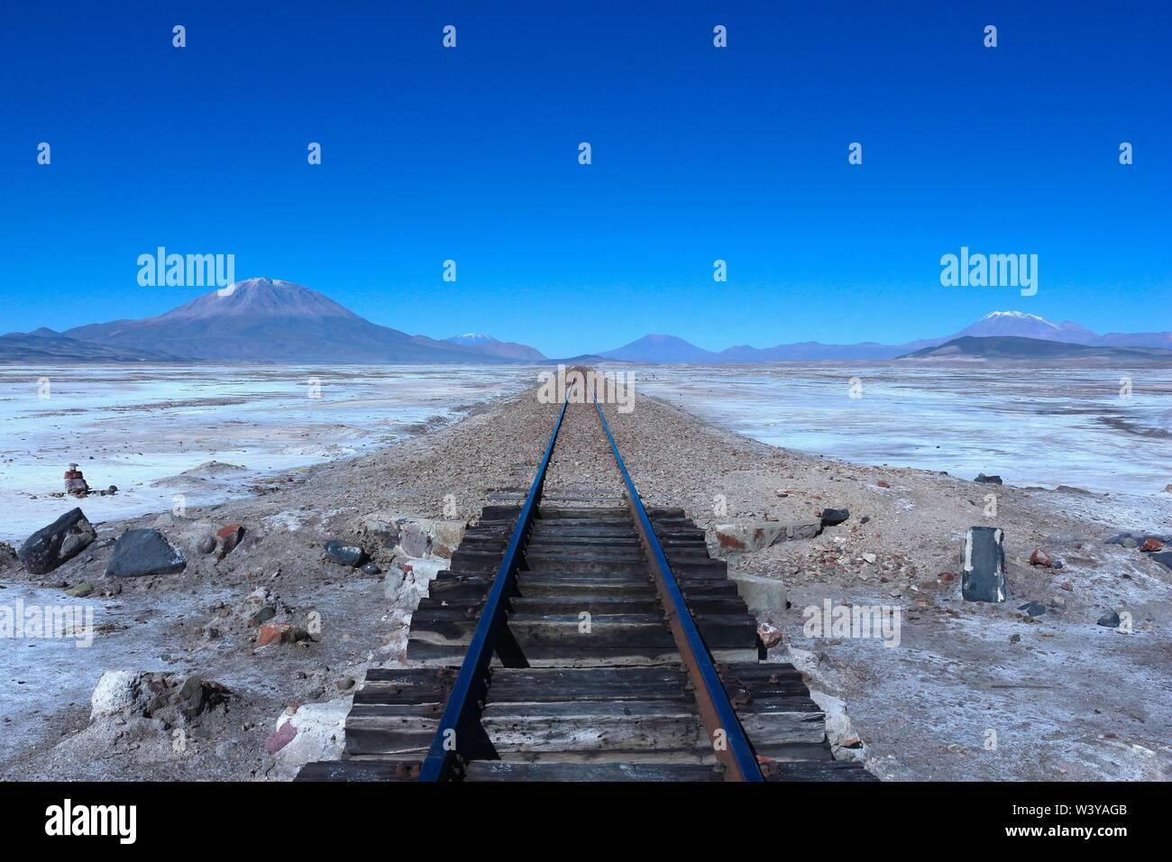 Vía del tren al infinito con volcanes en la espalda, el Salar de Uyuni, Bolivia Foto de stock