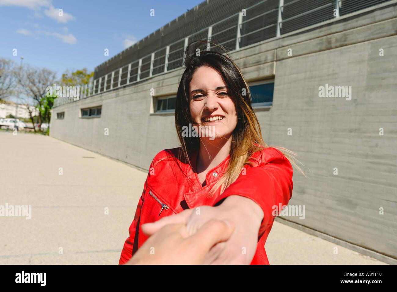 Joven de chaqueta roja sosteniendo su mano por su novio sonriendo. Imagen De Stock