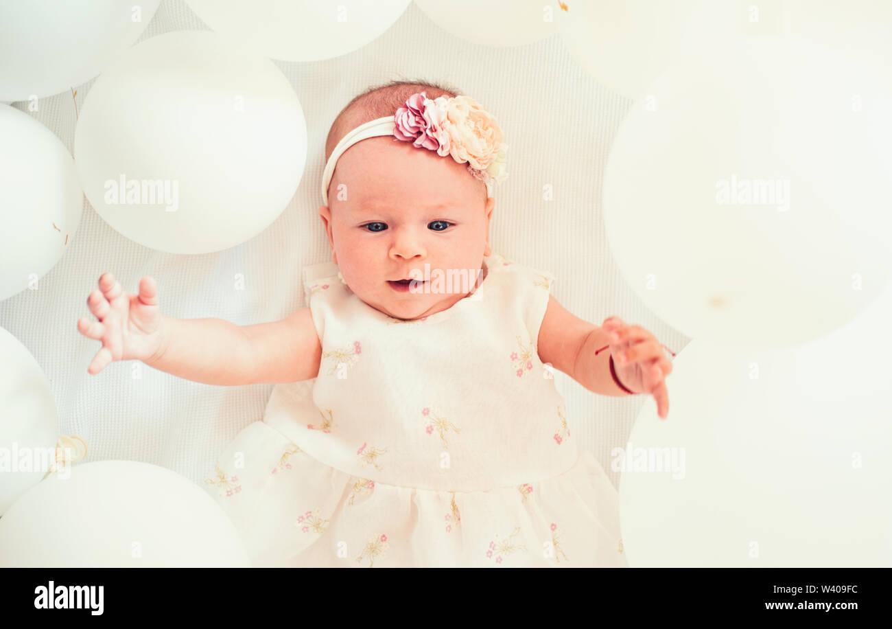 Mi dulce bebé. La familia. El cuidado de los niños. Día de los niños. La pequeña niña. Feliz cumpleaños. Felicidad infantil. Retrato de niño feliz en globos blancos. S Imagen De Stock