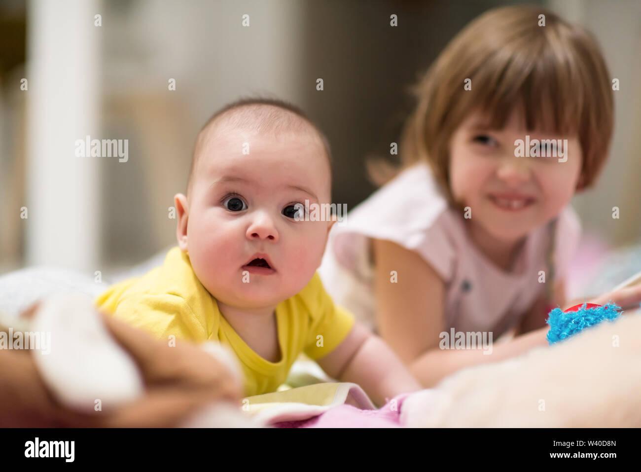 Familia feliz Little Sister y su hermano bebé acostado mientras juega en el suelo cubierto con mantas en casa Imagen De Stock