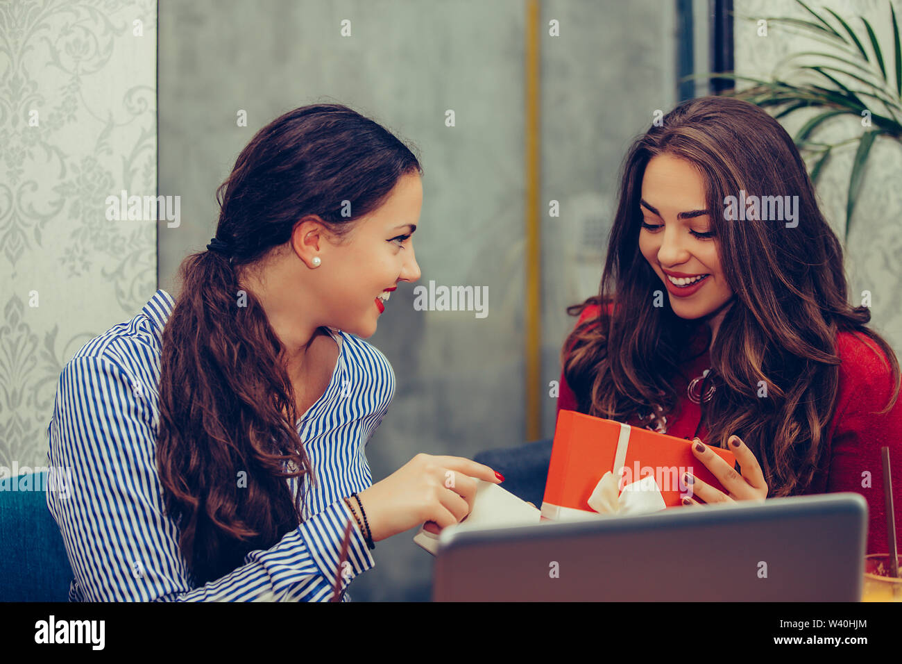 Hermosa joven sentado en el café con su amiga y recibir un regalo. Foto de stock