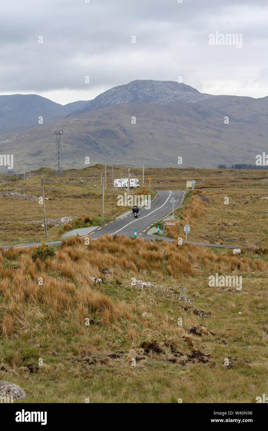 Abrir camino a través de bog tierras en el oeste de Irlanda con un motociclista y autocaravana en una carretera rural hacia Connemara, en el Condado de Galway. Foto de stock