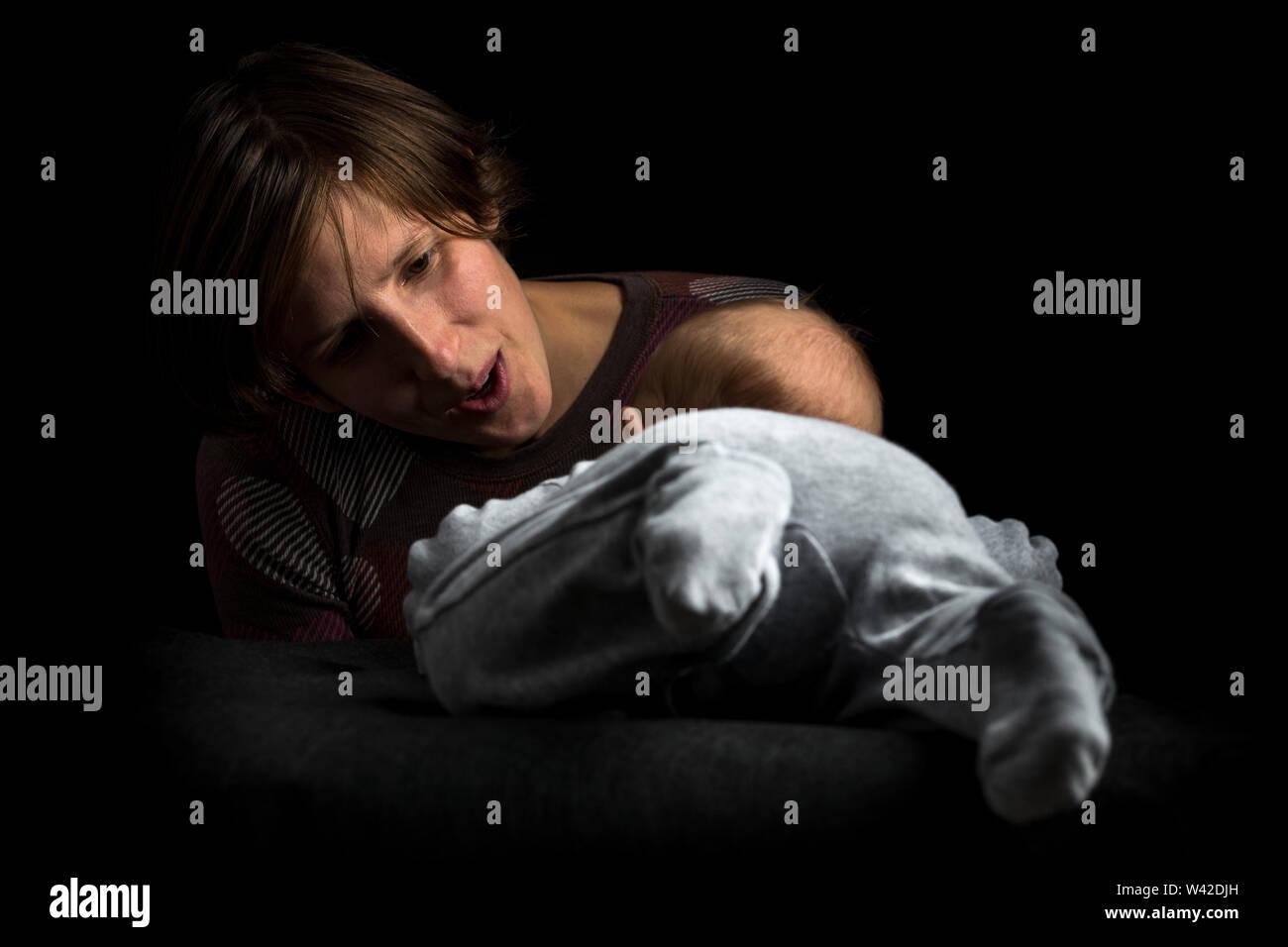 Edad media madre jugando con su bebé en posición decúbito prono. Aislado sobre fondo negro. Imagen De Stock