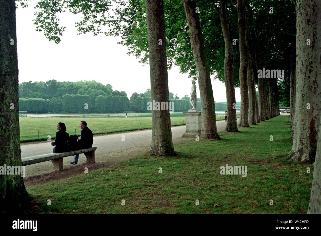 En el jardín de Versalles, después de caminar por los enormes terrenos de Versalles, dos turistas estadounidenses se toman un respiro muy necesario, Foto de stock