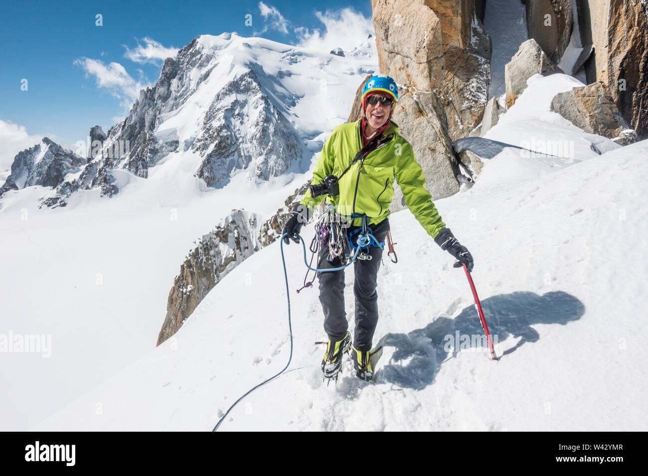 Un escalador sonríe mientras disfruta de excelentes condiciones en los Alpes franceses Foto de stock