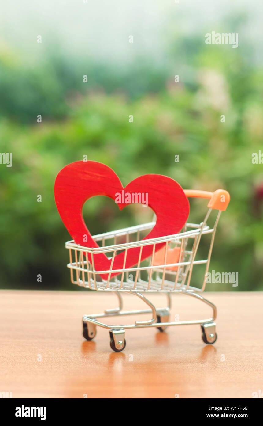 Corazón de madera roja en el trading cart. concepto de la compra de amor. La naturaleza de fondo. Salud y compra de medicamentos. Presupuesto de atención de la salud. Amor a s Foto de stock