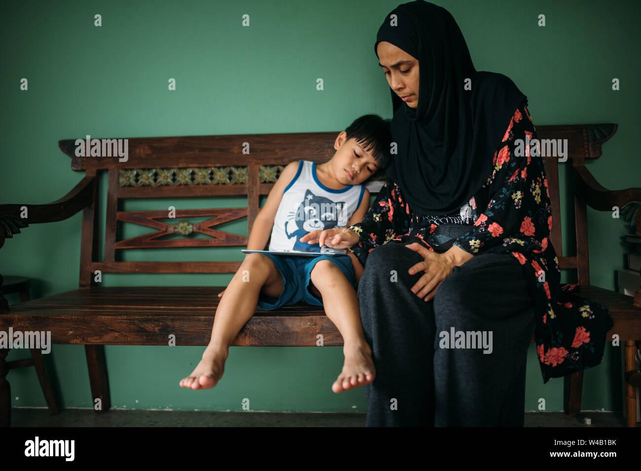Mujer asiática con hijo jugar en smart tablet Foto de stock