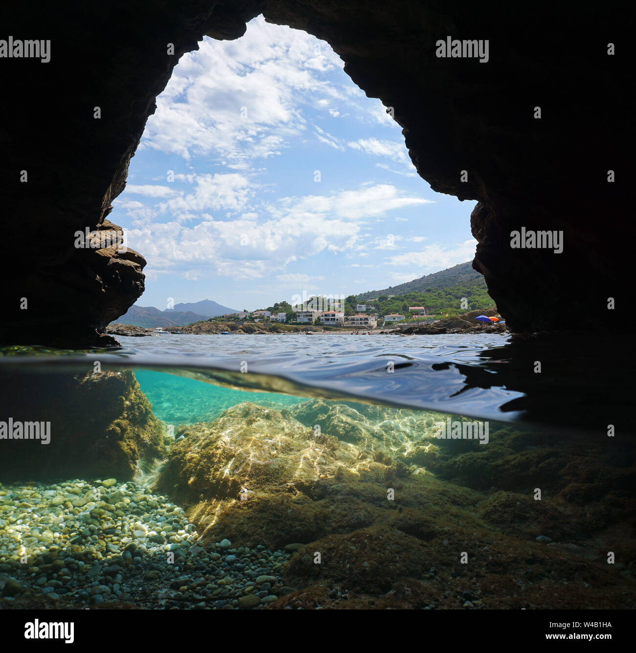 Costa desde el interior de una cueva en la orilla del mar, vista dividida sobre y bajo el agua, el mar Mediterráneo, España, el Port de la Selva, Costa Brava, Cataluña Foto de stock